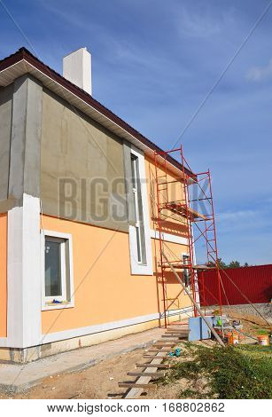 Close up on painting house wall. Construction or repair of the rural house with eaves windows chimney fixing facade insulation plastering and painting outdoor. House facade construction