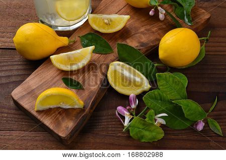 Still life of a group of lemons, whole and cut, on a cutting board. Leaves and lemon flowers with a glass of fresh squeezed lemonade found out the scene.