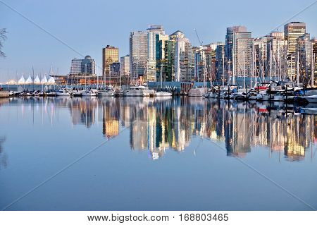 Vancouver Skyline and reflection in calm water. Coal Harbor. View from Stanley Park. West End. Downtown Vancouver. British Columbia. Canada.