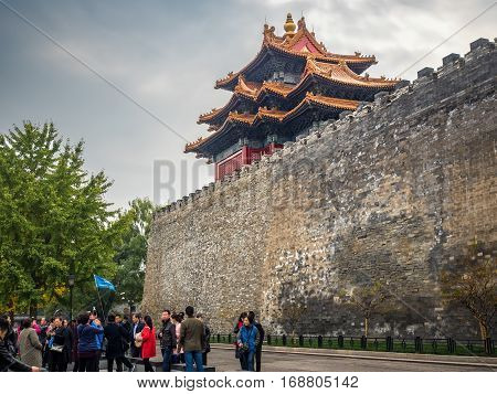 Beijing, China - Oct 30, 2016: View of Jiaolou Tower, Forbidden City (Gu Gong, Palace Museum). This ancient watch tower is along Donghuamen Road. Visitors can commonly be seen outside the wall.