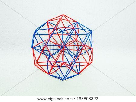 Red and blue handmade three-dimensional model of geometric solid on a white textured background.