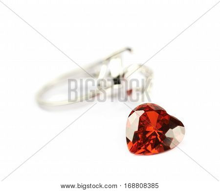 Silver ring with a red heart shaped gem fallen off it isolated over the white background