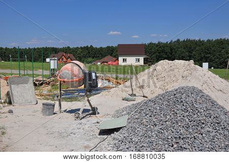 Cement mixer machine at construction site tools and sand. Construction Site with cement mill at Dusk