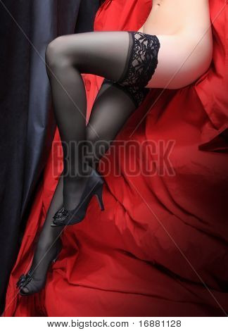 Beautiful slim legs in black nylons on a red background.