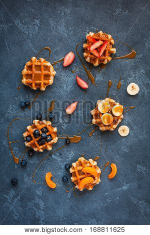 Traditional belgian waffles with fresh fruit and caramel on stone background. Flat lay top view