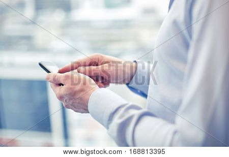 business, technology and people concept - close up of man hands with smartphone texting message or dialing number at office