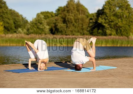 fitness, sport, yoga, people and healthy lifestyle concept - couple making headstand outdoors on river or lake berth