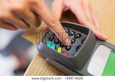 finance, money, technology, payment and people concept - close up of hand entering pin code to card reader terminal