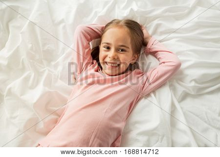people, children and bedtime concept - happy little girl lying in bed at home