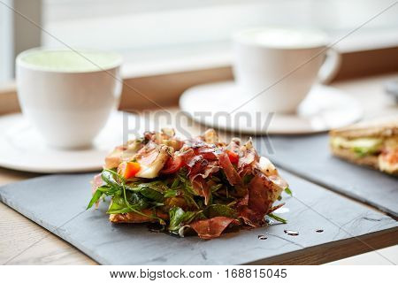 food, dinner, haute cuisine and eating concept - prosciutto ham salad on stone plate and coffee cups at restaurant