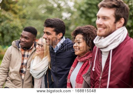 people, friendship and international concept - group of happy friends outdoors