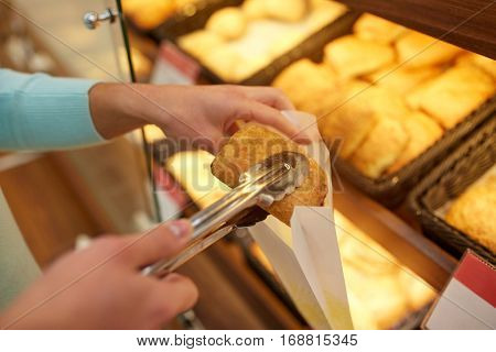 food, baking and sale concept - close up of hand with tongs and paper bag buying bun at bakery or grocery store