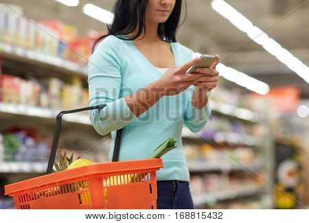 consumerism, technology and people concept - woman with smartphone and shopping basket buying food at grocery store or supermarket