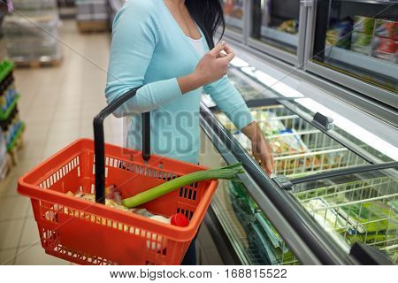 sale, shopping, consumerism and people concept - close up of woman with food basket at grocery store freezer
