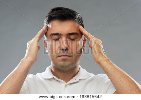 people, mind, conscious and pain and concept - man suffering from head ache or thinking over gray background