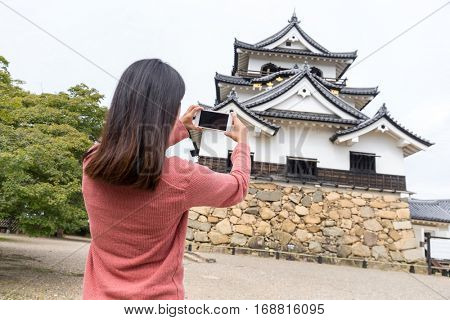 Woman taking photo with mobile phone on Hikone castle