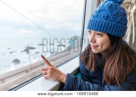 Woman pointing out of the location inside train compartment