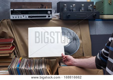 Retro styled image of a collection of old vinyl record lp's with sleeves on a wooden background. Browsing through vinyl records collection. Music background. Copy spase.