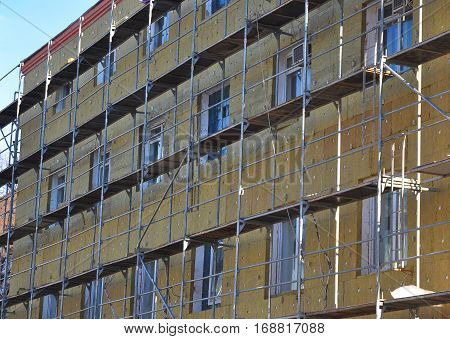 Energy efficiency house wall renovation for energy saving. Exterior house wall heat insulation with mineral wool building hospital under construction.