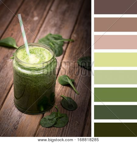 Fresh green smoothie on an old wooden table, in a glass jar with a straw, in a colour palette with complimentary colour swatches.
