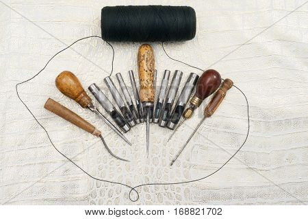 Leather craft tools on a leather background. Craftsman work desk . Piece of hide and working handmade tools on a work table. Top view. Copy space.