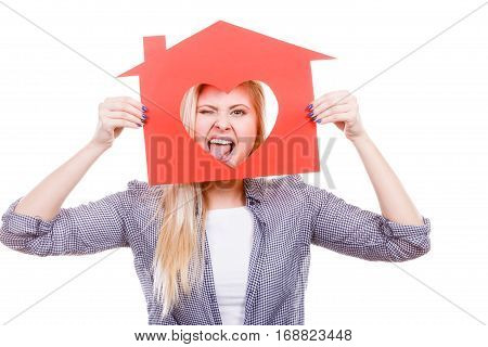 Ownership and property concept. Happy woman holding red paper house with hole in heart shape loving new home folling around and sticking tongue out