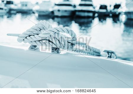 Close-up nautical knot rope tied around stake on boat or ship boat mooring rope.