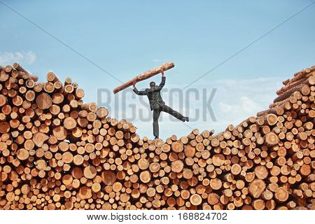 balancing business man on top of large pile of cut wooden logs , lifting heavy log