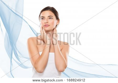 Young woman looking away while touching her face isolated on white background. Beauty girl after spa treatment with copy space on right side and blue waves of cloths. Beauty and skincare therapy.
