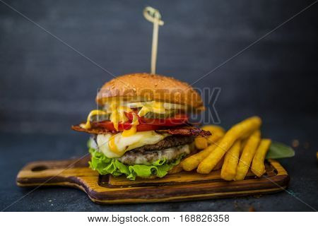 Tasty grilled beef  burger with lettuce and mayonnaise in crispy shortbread with lettuce and mayonnaise served with french fries on small cutting board.