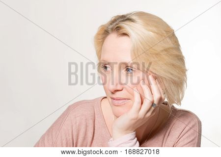Potrait of a blonde lady looking away with her chin resting on one hand.