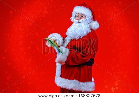 Christmas concept. Portrait of a fairytale Santa Claus turned sideways over red bakground. Good old traditions. Family holidays.