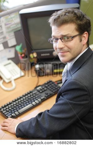 Young white man siting at the desk and working on personal computer