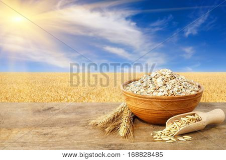 Oat flakes in bowl. Ears of oats and oatmeal in bowl on table with field on the background. Agriculture and harvest concept. Ripe oats field, blue sky with beautiful clouds and sun. Uncooked porridge