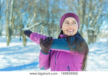 Fitness young woman stretching her hand outdoors. Runner girl stretching after running. Girl wearing sportswear and doing stretching exercises. Winter sports, outdoor fitness, workout, health concept poster