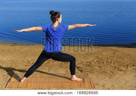 Woman practicing yoga outdoors on the beach. Female doing yoga warrior or virabhadrasana pose on the nature water background. Yoga, sport, fitness, stretching, healthy lifestyle concept