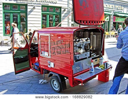 Aarhus, Denmark - June 6, 2009: A man sells coffee specialties in a pedestrian area of downtown of Aarhus in Denmark. The espresso machine is installed in a little red tricycle Italian car.