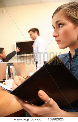 Group of three business people working at the office.woman in focus