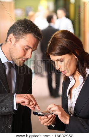 A businessman explains how to use a cellphone as an appointment calendar to his female partner.