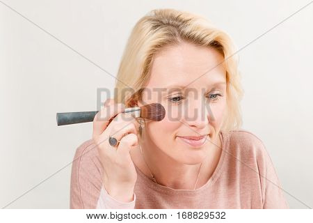 Lady Applying Blush With A Brush