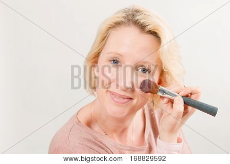 Blonde Lady Gazing Directly And Applying Make-up On Cheek