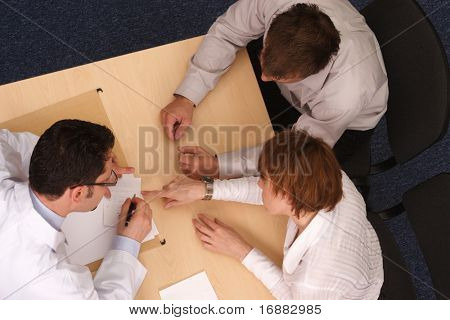 male doctor explaining diagnosis and medication to caucasian couple