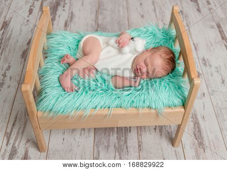 beautiful sleeping baby in jumper on wooden cot with turquoise fluffy blanket