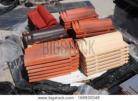 Building and construction materials colored roof tiles organized on pallets for sale