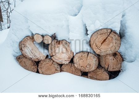 Snow Log Stack Lumber In Winter. Woodpile Of Pine