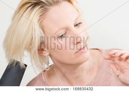 Blonde Lady Drying Her Hair With Electric Blow Dryer