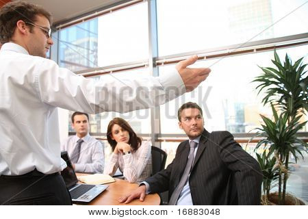 man  showing the results  to the group of business people at the meeting