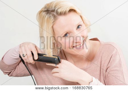 Smiling Lady Styling Her Hair With Straghtening Iron