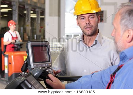 male engineer talking to forklift operator in warehouse