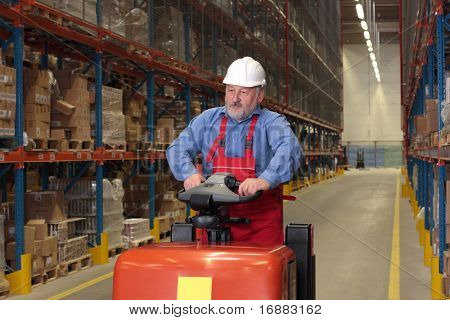 A senior worker driving the fork lift through a storage room in a factory poster